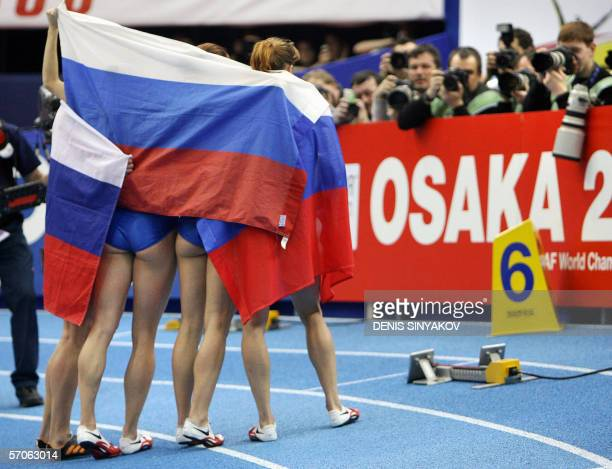 The Russian team wrapped in its country's flag poses for photographers after winning the women's 4x400 meters relay ahead of The United States and...