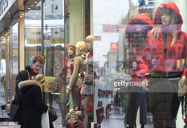 TO GO WITH AFP STORY 'Goodbye Lenin hello shopping Russia's middle class takes root' A Russian couple stands outside a shop at the popular pedestrian...