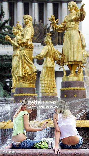 Two girls chat as temperatures soared over 30 degrees Celsius beside a fountain representative of the friendship of nations of the former Soviet...