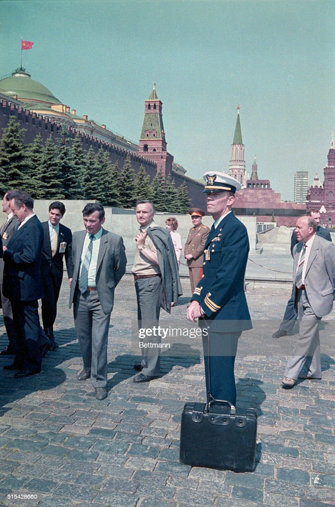 Lieutenant Commander Woody Lee stands with a briefcase attached to his wrist by a leather strap in Red Square as President Reagan toured the square with Mikhail Gorbachev. The briefcase, commonly known as 'The Football,' contains codes needed for the president to give orders to use nuclear weapons and is carried near the president at all times.
