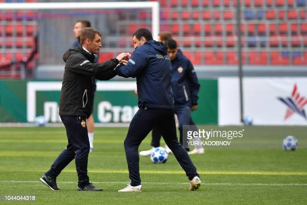 Moscow's Belarus coach Viktor Goncharenko jokes with CSKA Moscow's Russian midfielder Alan Dzagoev during a training session at Moscow's VEB Arena on...
