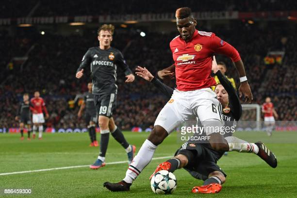 Moscow's Brazilian defender Mario Fernandes tackles Manchester United's French midfielder Paul Pogba during the UEFA Champions League Group A...