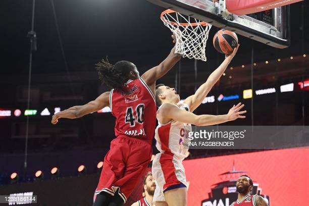 Moscow's guard Alexander Khomenko jumps for the net next to Olimpia Milano's Jeremy Evans during the Basketball Euroleague Final Four championship...