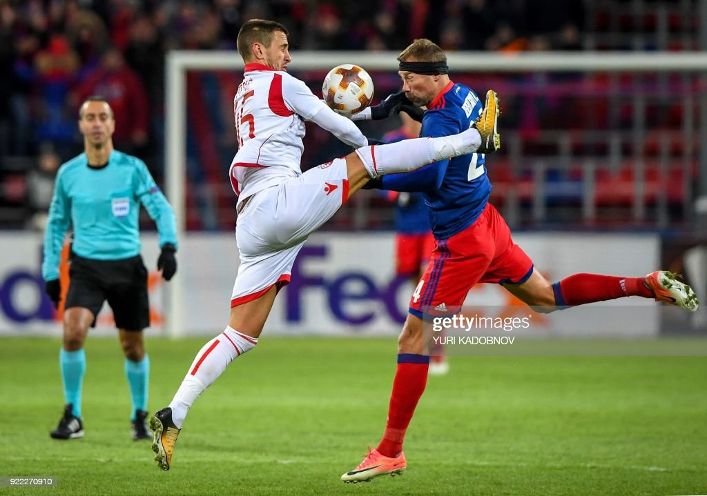 Moscow's Russian defender Vasili Berezutski (R) vies with Crvena Zvezda Beograd's forward from Serbia Aleksandar Pesic (L) during the Europa League Round of 32 second leg football match between CSKA Moscow and Crvena Zvezda Beograde in Moscow on February 21, 2018. / AFP PHOTO / Yuri KADOBNOV