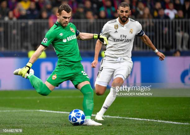 Moscow's Russian goalkeeper Igor Akinfeev kicks the ball next to Real Madrid's French forward Karim Benzema during the UEFA Champions League group G...