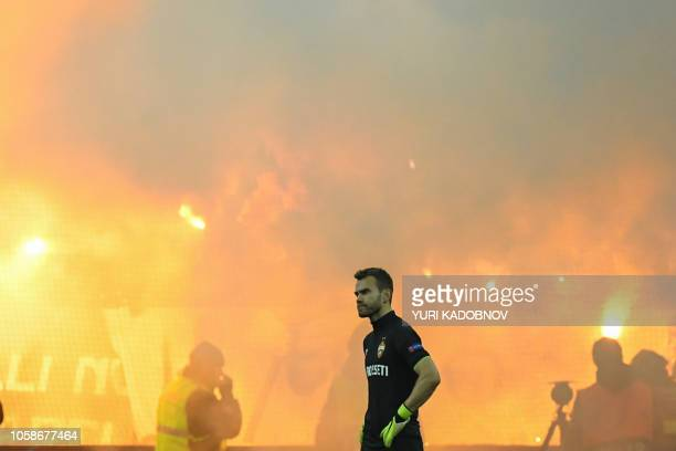 Moscow's Russian goalkeeper Igor Akinfeev walks on the pitch as fans light flares during the UEFA Champions League group G football match between PFC...