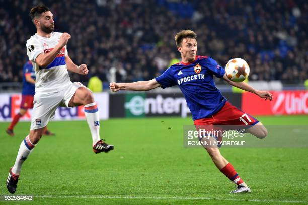 Moscow's Russian midfielder Alexandre Golovin kicks the ball next to Lyon's French midfielder Jordan Ferri during the UEFA Europa League round of 16...