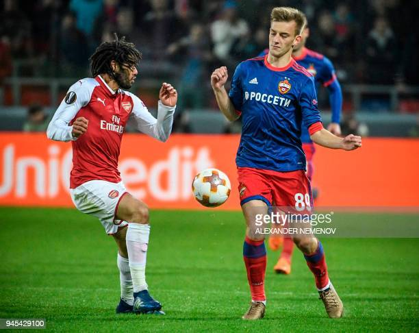 Moscow's Russian midfielder Konstantin Kuchayev vies for the ball against Arsenal's Egyptian midfielder Mohamed Elneny during the UEFA Europa League...