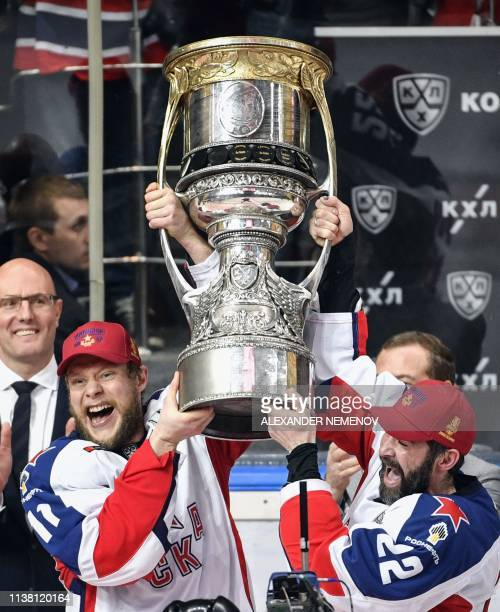 Moscow's Sergei Andronov and Alexander Popov hold the trophy as they celebrate their victory over Avangard Omsk after the Gagarin Cup 2019 final...