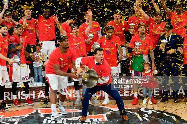 Moscow's US centre Kyle Hines and CSKA Moscow's Greek coach Dimitris Itoudis hold the trophy after winning the EuroLeague final basketball against...