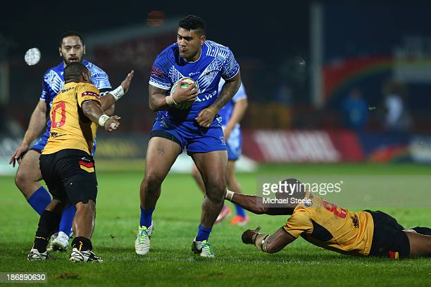 Mose Masoe of Samoa cuts between Larsen Marabe and Mark Mexico of Papua New Guinea during the Rugby League World Cup Group B match between Papua New...
