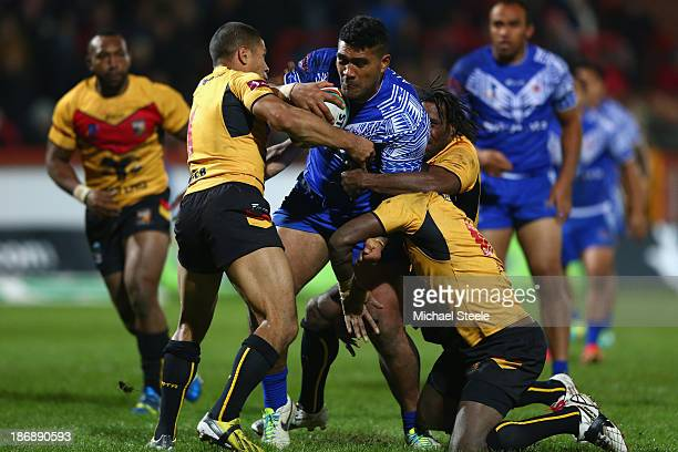 Mose Masoe of Samoa is held up by David Mead and Charlie Wabo of Papua New Guinea during the Rugby League World Cup Group B match between Papua New...