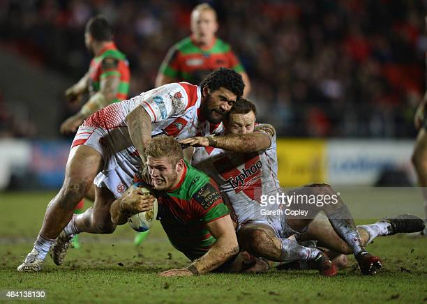 Mose Masoe of St Helens assists in tackling Tom Burgess of South Sydney Rabbitohs during the World Club Challenge match between St Helens and South...