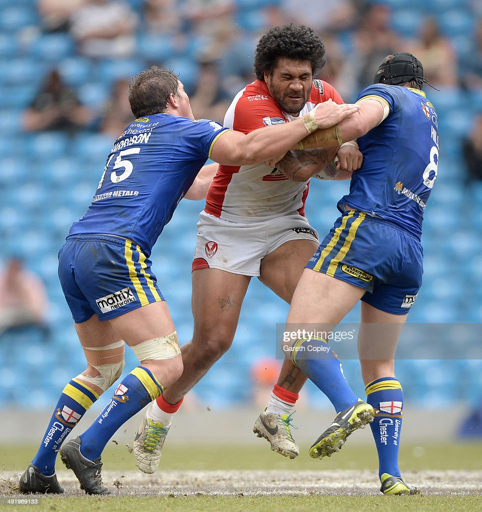 Mose Masoe of St Helens is tackled by Ben Harrison and Chris Hill of Warrington Wolves during the Super League match between Warrington Wolves and St Helens at Etihad Stadium on May 18, 2014 in Manchester, England.