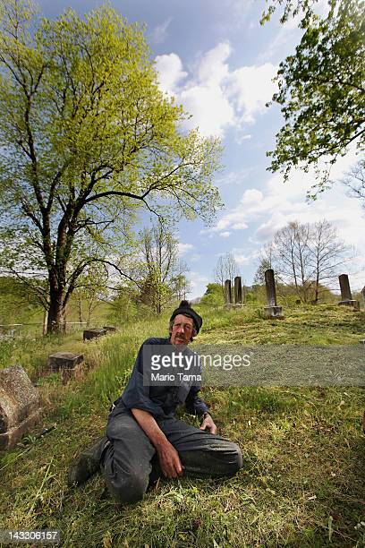 Mose Noble looks on while taking a break from cleaning a graveyard in Owsley County on April 16 2012 in Booneville Kentucky Noble is a former chimney...
