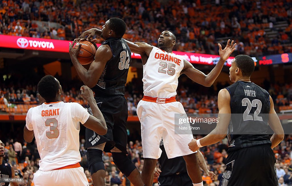 Moses Ayegba #32 of the Georgetown Hoyas drives to the basket as teamate Otto Porter Jr. #22 looks on against Rakeem Christmas #25 and Jerami Grant #3 of the Syracuse Orange during the game at the Carrier Dome on February 23, 2013 in Syracuse, New York.