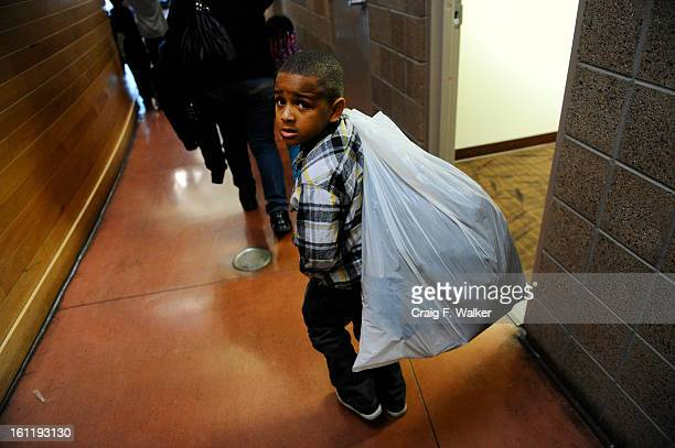 Moses Chaney carries toys after visiting Delta Eta Boule's Toys For Tots Christmas Celebration at the Hiawatha Davis Recreation Center in the Park...