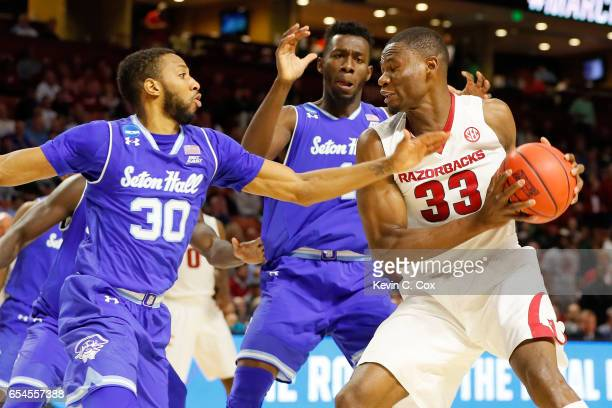 Moses Kingsley of the Arkansas Razorbacks with the ball against Madison Jones of the Seton Hall Pirates in the first round of the 2017 NCAA Men's...