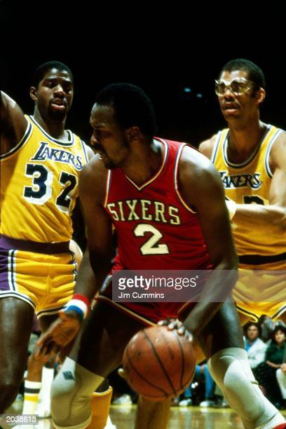 Moses Malone of the Philadelphia 76ers dribbles against Magic Johnson and Kareem Abdul-Jabbar of the Los Angeles Lakers during the 1983 NBA Finals at...