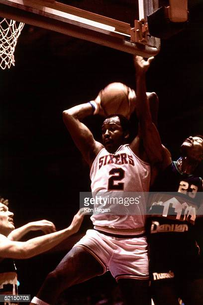 Moses Malone of the Philadelphia 76ers drives to the basket against the Denver Nuggets during an NBA game in 1983 at the Spectrum in Philadelphia,...