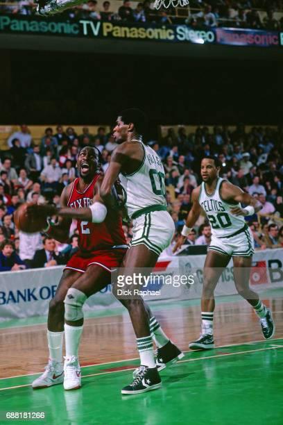Moses Malone of the Philadelphia 76ers looks to shoot the ball against Robert Parish of the Boston Celtics circa 1985 at the Boston Garden in Boston...