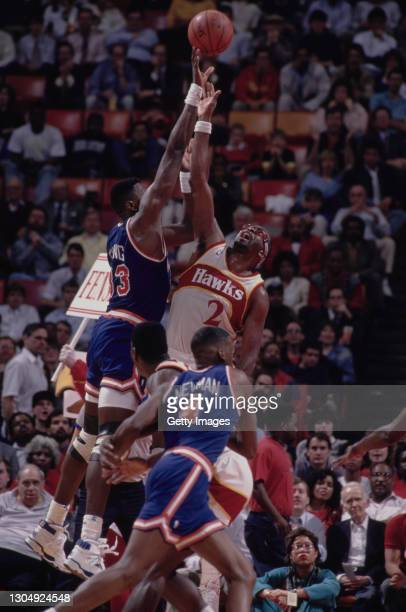 Moses Malone, Power Forward and Center for the Atlanta Hawks and Patrick Ewing of the New York Knicks reach for the basketball during their NBA...