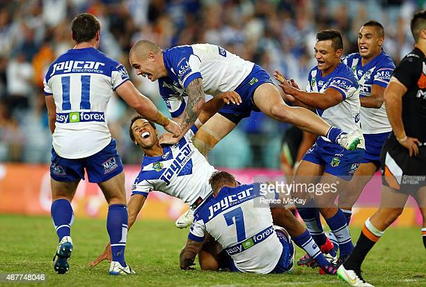 Moses Mbye of the Bulldogs celebrates his winning field goal in golden point time during the round four NRL match between the Wests Tigers and the...