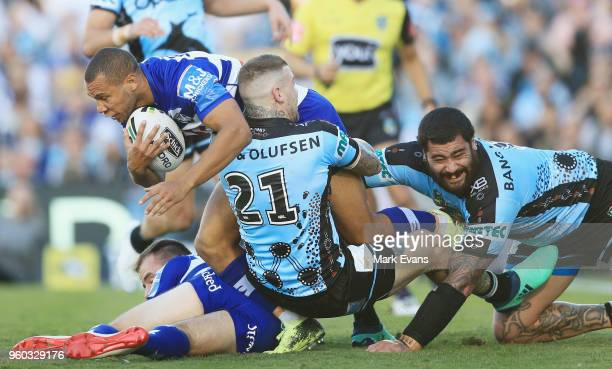 Moses Mbye of the Bulldogs is tackled by Josh Dugan and Andrew Fifita of the Sharks during the round 11 NRL match between the Cronulla Sharks and the...