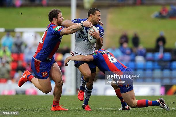 Moses Mbye of the Bulldogs is tackled by the Knights defence during the round 22 NRL match between the Newcastle Knights and the Canterbury Bulldogs...