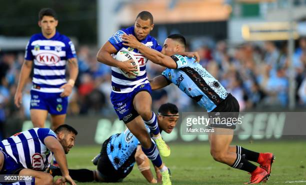 Moses Mbye of the Bulldogs is tackled by Valentine Holmes of the Sharks during the round 11 NRL match between the Cronulla Sharks and the Canterbury...