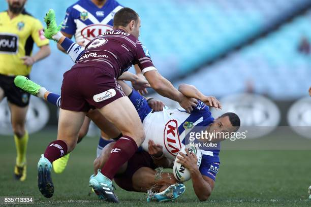 Moses Mbye of the Bulldogs is tackled during the round 24 NRL match between the Canterbury Bulldogs and the Manly Sea Eagles at ANZ Stadium on August...