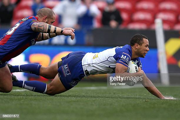 Moses Mbye of the Bulldogs scores a try during the round 22 NRL match between the Newcastle Knights and the Canterbury Bulldogs at Hunter Stadium on...