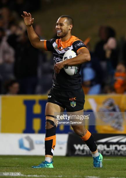 Moses Mbye of the Tigers celebrates after scoring a try during the round 24 NRL match between the Wests Tigers and the Manly Sea Eagles at...