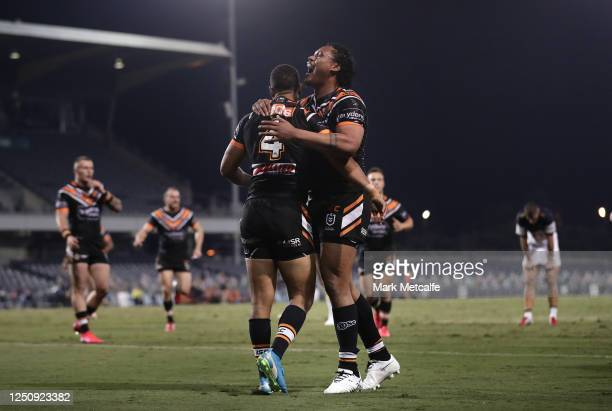 Moses Mbye of the Tigers celebrates with Luciano Leilua of the Tigers after scoring a try during the round six NRL match between the Wests Tigers and...
