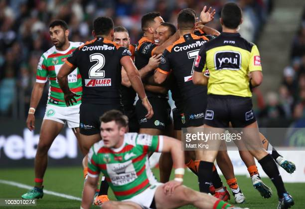 Moses Mbye of the Tigers celebrates with team mates after scoring a try during the round 19 NRL match between the Wests Tigers and the South Sydney...