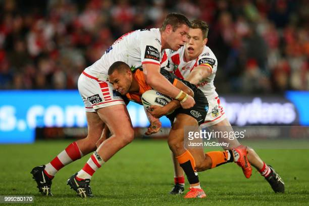 Moses Mbye of the Tigers is tackled by Jeremy Latimore and Cameron McInnes of the Dragons during the round 18 NRL match between the St George...