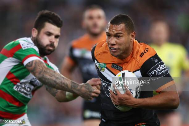 Moses Mbye of the Tigers takes on the defence during the round 19 NRL match between the Wests Tigers and the South Sydney Rabbitohs at ANZ Stadium on...