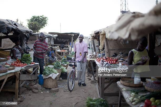 Moses Mndhlovu age 29 a field officer walks with his bicycle past a market as he tracks stoves with a GPS Cook stoves supplied by Clean Development...