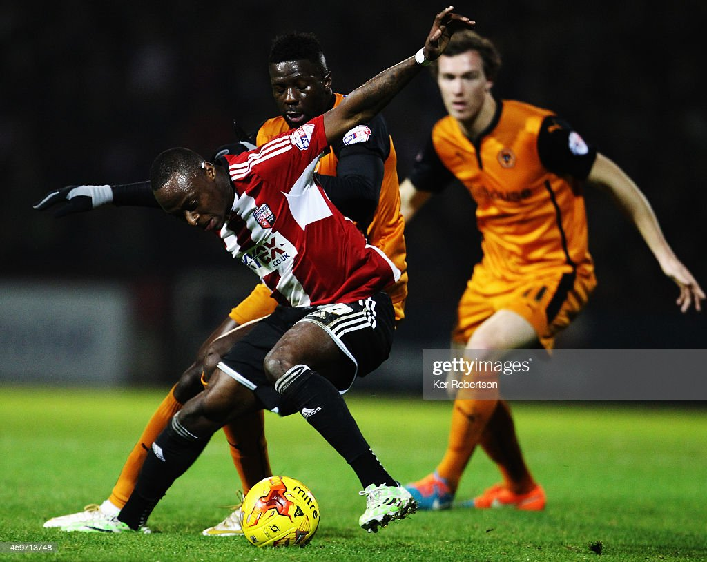 Moses Odubajo of Brentford holds off the challenge of Bakary Sako of Wolverhampton Wanderers during the Sky Bet Championship match between Brentford and Wolverhampton Wanderers at Griffin Park on November 29, 2014 in Brentford, England.