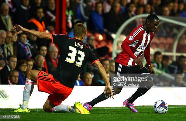 Moses Odubajo of Brentford looks to get past Fulham's Dan Burn during the Capital One Cup Second Round match between Brentford and Fulham at Griffin...
