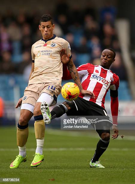 Moses Odubajo of Brentford tackles with Matthew Briggs of Millwall during the Sky Bet Championship match between Millwall and Brentford at The Den on...
