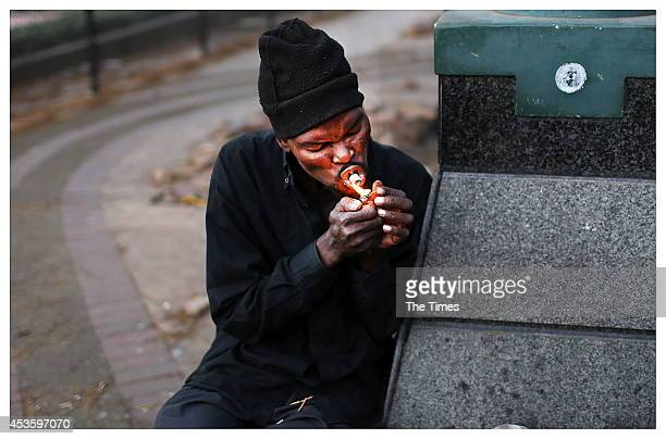Moses Sehoole lights up a crack pipe on August 12 2014 in Pretoria South Africa Members of Moeggesukkel a nonprofit antidrugs organization led by...