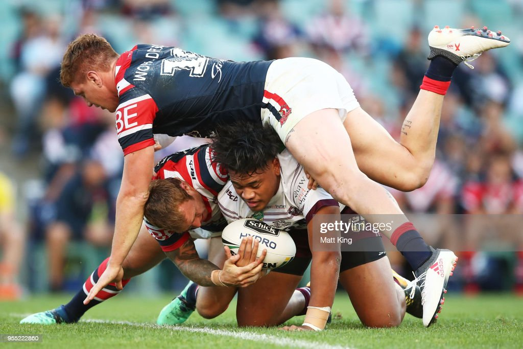 Moses Suli of the Sea Eagles is tackled by Dylan Napa of the Roosters (top) and Jake Friend of the Roosters (bottom) during the round nine NRL match between the Sydney Roosters and the Manly Warringah Sea Eagles at Allianz Stadium on May 6, 2018 in Sydney, Australia.