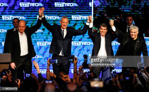 Moshe Yaalon Benny Gantz Gabi Ashkenazi and Yair Lapid of the Blue and White political alliance hold hands together as they appear before supporters...