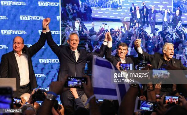 TOPSHOT Moshe Yaalon Benny Gantz Gabi Ashkenazi and Yair Lapid of the Blue and White political alliance hold hands together as they appear before...