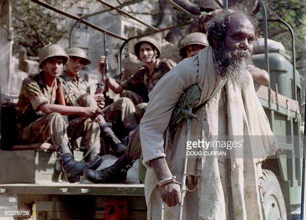 Moslem man walks on crutches near an Indian army patrol 15 January 1993 as communal HinduMoslem riots subsided after more than 10 days of violence...