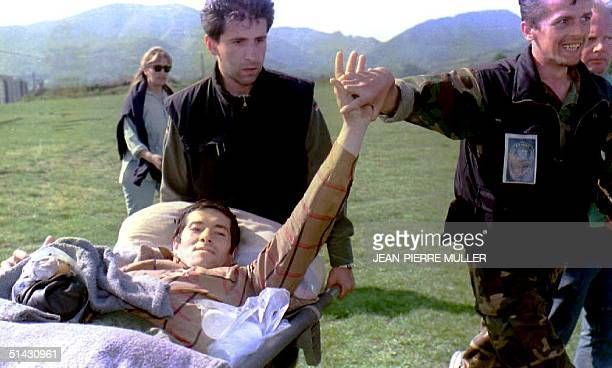 Moslem soldier holds an injured comrade's hand12 May 1993 after about 45 evacuees from the eastern Moslem enclave of Zepa arrived via UN helicopter...