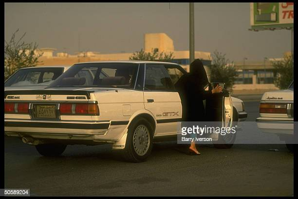 Moslem woman chadorcovered in modesty flashing wellturned ankle as she climbs into passenger seat of Toyota car in postgulf war Riyadh Saudi Arabia
