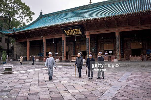 XI'AN SHAANXI CHINA Moslems walk out of the main hall for worship of the Xi'an Great Mosque With the huge eaves and brackets its roof is covered with...