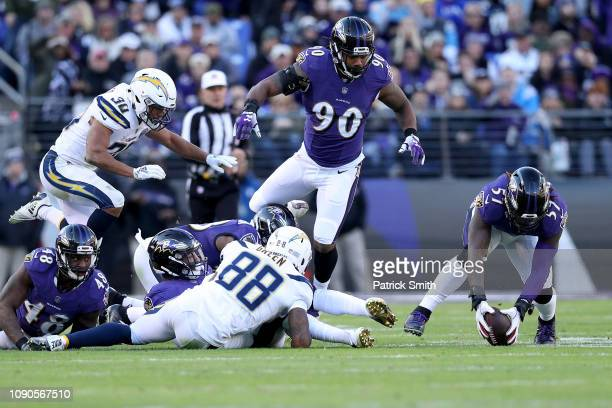 J Mosley of the Baltimore Ravens recovers a fumbled ball by Virgil Green of the Los Angeles Chargers during the third quarter in the AFC Wild Card...